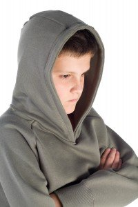 Young, hooded boy with crossed arms. He's on white background